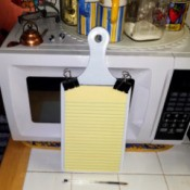 A small legal pad attached to a small cutting board with binder clips.
