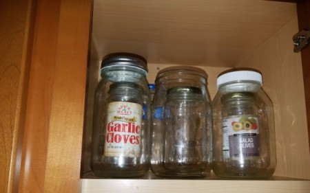 Small recycled glass jars stored inside larger jars in a cupboard.