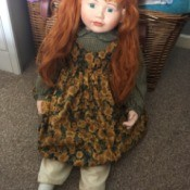 Age and Maker of a Porcelain Doll - red haired doll wearing a pinofore
