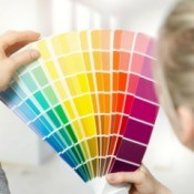 Woman selecting paint color from a color swatch catalog.