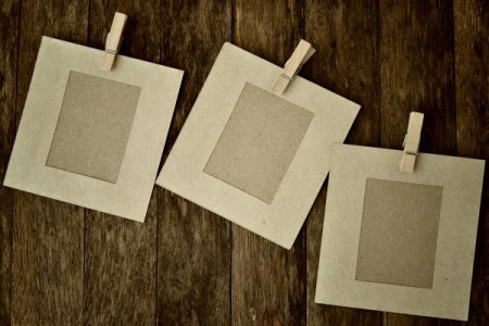 Paper picture frames with clothes pins on wood background.