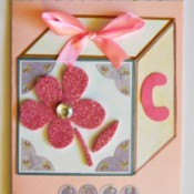 Baby's Toy Cube Card - glue rhinestone to center of flower and add a strip of washi tape to the top and trim ends