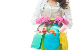 Woman holding a bucket full of cleaning supplies.