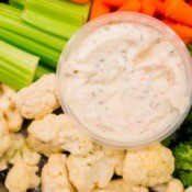 Bowl of ranch dip surrounded by the vegetables
