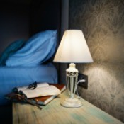 Bedside table with book lamp and glasses