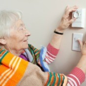 Elderly woman with a blanket around her shoulders adjusting her thermostat
