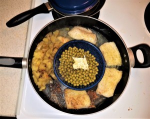 A pan cooking fish, potatoes and peas all at once.