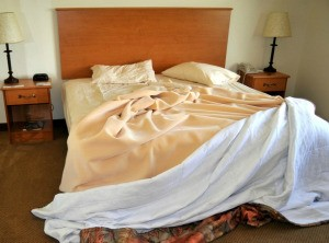 An unmade bed with blankets slipping off the end.