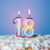 "A birthday cake with candles that show the number ""18""."