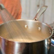 A saucepan with the contents being whisked and thickened.