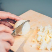 Hard boiled eggs being chopped into small pieces.