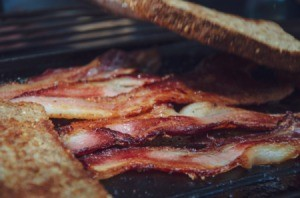 Bacon being cooked with slices of bread soaking up the grease.