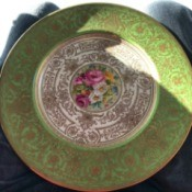 Value of Tiffany Plates by Cauldon - ornate gold filagree plate with green top edge and floral center