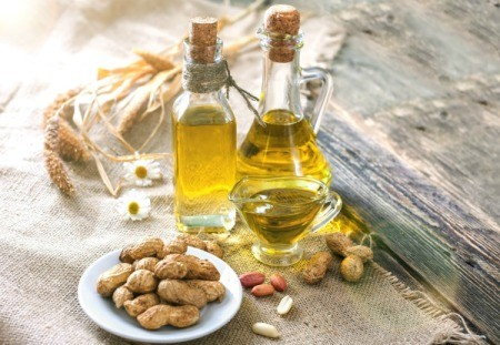 Peanut oil in 2 glass bottles with a plate of peanuts.