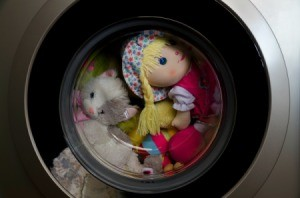 Doll and stuffed animals in a washing machine.