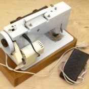 Sewing machine with it's foot pedal on the table.