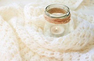 Candle in a jar with a crochet blanket.