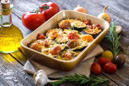 Eggplant And Zucchini Casserole on a wooden table with olive oil and other ingredients around dish