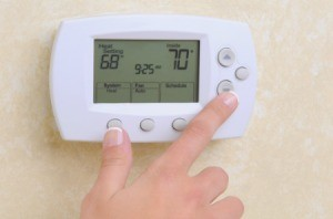 Hand adjusting the thermostat.