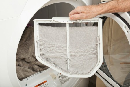 Hand pulling lint trap out of dryer.