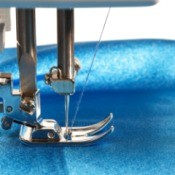 Sewing machine foot and needle on blue fabric.