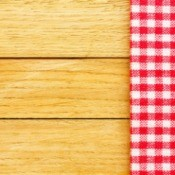Checkered Tablecloth On The Brown Wooden Background.