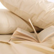 Beige pillow cases on a bed with an open book.