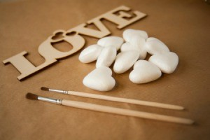 "Styrofoam hearts with a wooden cutout of the word ""love"" and some paintbrushes."