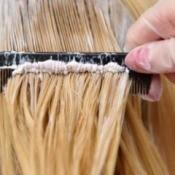 Woman having dye come through her blond hair