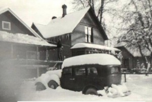 A black and white photo of a house with snow on the roof and on the old fashioned car in front.