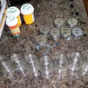 A row of small empty mason jars with prescription medication bottles.