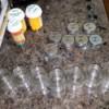 A row of small empty mason jars with prescription medication bottles.