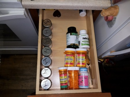 A row of mini mason jars in a drawer with medication for each day inside.