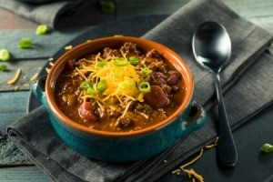 Chili in a bowl with grated cheese and a spoon on the side