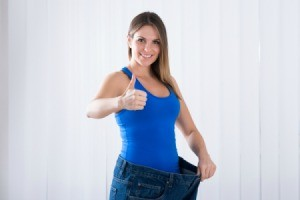 Woman wearing old pair of extra large jeans giving thumbs up