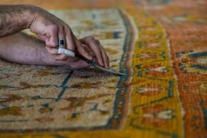 Man repairing a rug.