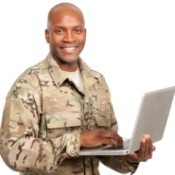 Soldier smiles while typing on a computer.