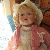Maker and Value of a Porcelain Doll - blond doll wearing a pink sweater