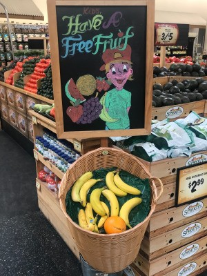 A sign at the grocery store with free fruit for kids while shopping.