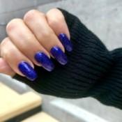 A hand with blue glittery nail polish.