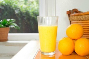 Orange juice in a glass next to a small stack of oranges