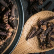Cloves on a wooded spoon.