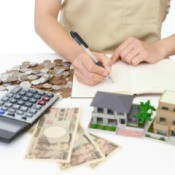 Woman calculating expenses, with money, calculator and a small house model.
