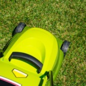 Electric lawn mower cutting grass