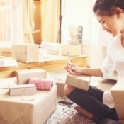 Woman surrounded by boxes, getting them ready to send.