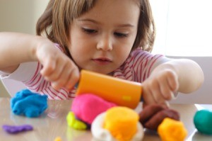 Child playing with many colors of Playdough