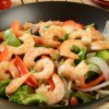 Shrimp and veggies being cooked in a wok