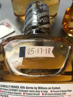 A date written on a post-it note attached to a bottle of Listerine.