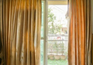 Sliding glass door with curtains partially drawn.