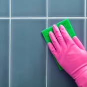 Hand in pink rubber glove scrubbing tile wall.